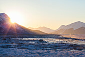 'Sunrise peaks over the Chugach Mountains into Turnagain Arm on an icy winter morning; Alaska, United States of America'