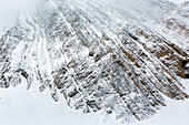 'Close up of a snow covered mountain face with line pattern from rock formation; Kananaskis Country, Alberta, Canada'