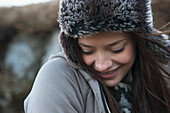 'Portrait Of A Young Woman Wearing A Fur Trimmed Hat And Looking Down; Iceland'