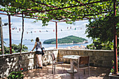 Young Woman on Covered Patio Looking Out Over Dubrovnik with Lokrum Island in Distance, Croatia