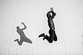 Portrait of Shirtless Young Adult Man Jumping with Shadow Cast Against Wall