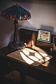 Light From Window on Small Writing Desk with Lamp in Shadows