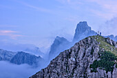 Person standing on summit and making photos, rock crags and clouds in background, Croz dell' Altissimo, Brenta group, UNESCO world heritage site Dolomites, Trentino, Italy