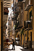 Narrow alley Via Orologio with many balconies and a working craftsman, Palermo, Sicily, Italy, Europe