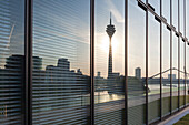 Television tower and Neuer Zollhof (Architect: F.O. Gehry) reflecting in the facade of the Hyatt Regency Hotel, Medienhafen, Duesseldorf, North Rhine-Westphalia, Germany