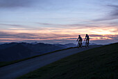 Two young men on their racing cycle at sunset in the Kitzbühler Alps, Kitzbühlerhorn, Tyrol, Austria