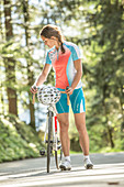 Young woman standing next to her racing cycle in the Kitzbühler Alps, Kitzbühlerhorn, Tyrol, Austria