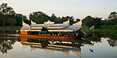 'A tour boat sails slowly down a tranquil river; Chiang Rai, Thailand'