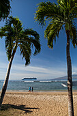 'Joggers on beach, cruise ship off of Puamana Beach just south of Lahaina town; Lahaina, Maui, Hawaii, United States of America'