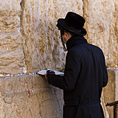'An orthodox jew standing at the Wailing Wall, old city of Jerusalem; Jerusalem, Israel'