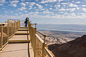'A tourist stands at the end of a lookout with a view of the Dead Sea region and the desert; South District, Israel'