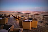 'Tische und Stühle auf einer Terrasse mit Blick auf die Wüste Negev und Ramon Krater; Mitzpe Ramon, Süddistrikt, Israel'