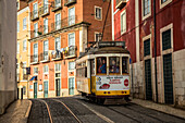 'A tram travels down the tracks beside buildings, Alfama; Lisbon, Portugal'