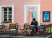 'A man sits alone on an outdoor patio of a cafe; Prague, Czech Republic'