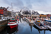 'Boats moored in a harbour with rugged mountains along the coastline; Svolvar, Lofoten Islands, Nordland, Norwa'