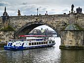 'A tour boat passing under Charles Bridge on the Vltava River; Prague, Czech Republic'