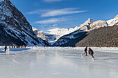 'Tourists enjoy ice skating on the frozen lake on a sunny day with this scenic mountain view; Lake Louise, Alberta, Canada'