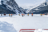 'A pair of hockey teams compete in pond hockey on Lake Louise at the Fairmont Chateau Lake Louise pond hockey tournament in the winter; Lake Louise, Alberta, Canada'