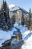 'Winter trails along Lake Louise in Banff National Park, the river is not fully frozen at the edge of the Fairmont Chateau Lake Louise Resort shown against the mountains in the background; Lake Louise, Alberta, Canada'
