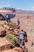 'A native american worker photographs tourists at the Skywalk Viewpoint over the West Grand Canyon natural landscape area in Arizona, a popular tourist attraction operated by the indigenous native American people; Arizona, United States of America'