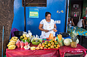 'A female vendor works cutting fruit at a stand selling fresh fruit; Nicaragua'