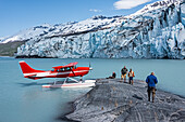 Tourists on a rock outcrop in front of Colony Glacier and Lake George, Southcentral Alaska, USA