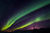 'Colourful Aurora borealis over a man with arms outstretched silhouetted against light pollution from nearby Fort Greely; Alaska, United States of America'