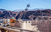 Looking down on the hoover dam to see the roadway across the dam and the unique construction of the electric power lines that connect through the hydroelectric dam, Arizona, United States of America