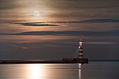 Roker Lighthouse glowing at the end of a pier under a bright full moon reflecting on tranquil water, Sunderland, Tyne and Wear, England
