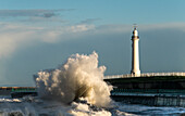 A large wave crashing against the wall on the shoreline below a lighthouse, Sunderland, Tyne and Wear, England