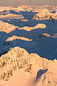 Peaks of a snow covered mountain range glowing pink at sunset, Kachemak Bay State Park, Alaska, United States of America