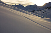 Snow covered slope in a mountain range at sunset, Alaska, United States of America