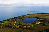 A lake and winding road off Kachemak Bay with a view of the Kenai Mountains, Kachemak Bay State Park, Homer, Alaska, United States of America