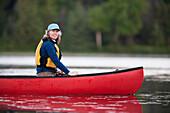 A woman canoeing on Stone Step Lake, Homer, Alaska, United States of America