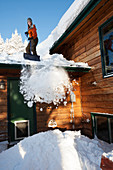 A young woman removes snow from the roof of her house, Homer, Alaska, United States of America
