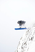 A snowboarder jumps off a mountain cliff, Alaska, United States of America