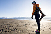 A young woman stretches on the wet beach before running, Homer, Alaska, United States of America