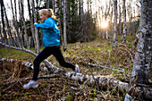A young woman running over logs on a forest floor in a forest, Homer, Alaska, United States of America