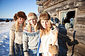 Portrait of three girls standing by a log cabin wearing fur hats, Homer, Alaska, United States of America
