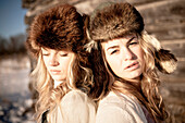 Portrait of two girls standing by a log cabin wearing fur hats, Homer, Alaska, United States of America
