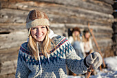 Portrait of a young woman wearing a hat and sweater by a log cabin in winter, Homer, Alaska, United States of America