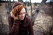 Portrait of a woman with red hair looking contemplative, Homer, Alaska, United States of America