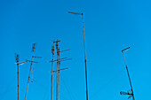 The typical aerials for analogous reception on a residential building in front of blue sky, Rome, Latium, Italy