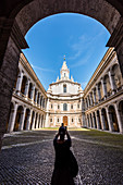 A tourist takes a photo of the inner courtyard of the baroque church Sant'Ivo alla Sapienza, Rome, Latium, Italy