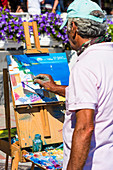 A local artist painting a picture of the steep coast at the promenade, Positano, Amalfi Coast, Campania, Italy