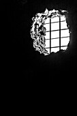 Black-and-white photo of an interior with barred breakthrough as a window, Pompeii, the Gulf of Naples, Campania, Italy