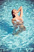 Woman enjoying warmth of sun while soaking in cool waters of pool