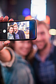 Young couple taking selfie while sightseeing in Times Square, New York City, New York, USA