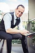 Man using digital tablet outdoors, smiling, portrait
