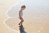 Little girl wading in the surf